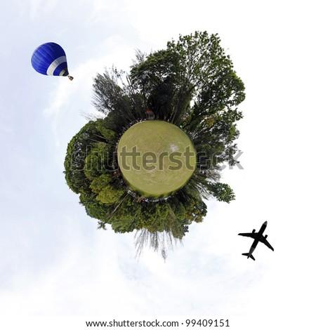 Airplane and hot air balloon circulating a tiny green planet.