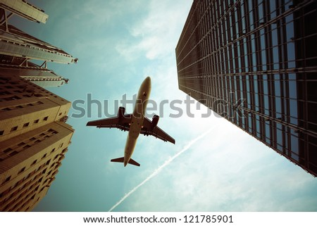 airplane and modern buildings with dramatic sky,abstract cityscape