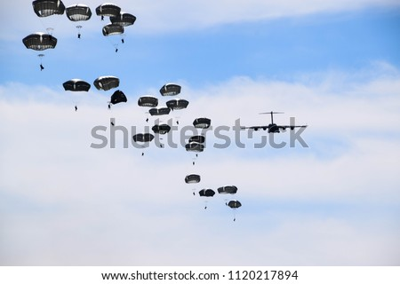 airplane and paratroopers with parachutes in the sky