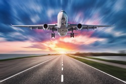 Airplane and road with motion blur effect at sunset. Landscape with passenger airplane is flying over asphalt road and colorful sky. Commercial plane is landing. Aircraft with blurred background