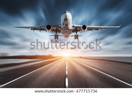 Airplane and road with motion blur effect at sunset. Landscape with passenger airplane is flying over the asphalt road and cloudy sky. Commercial plane is landing. Aircraft with blurred background  #677715736