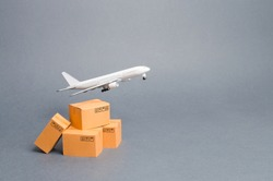 Airplane and stack of cardboard boxes. concept of air cargo and parcels, airmail. Fast delivery of goods and products. Cargo aircraft. Logistics, connection to hard-to-reach places. Air fleet supply.