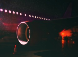 airplane at airport. night red eye flight. fragment of the body of aircraft. Business and travel concept