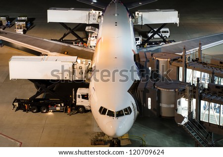 Airplane at gate during delivery catering service at night