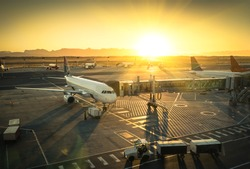 Airplane at the terminal gate ready for takeoff - Modern international airport during sunset - Concept of emotional travel around the world