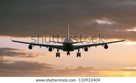 Airplane before landing in sunset