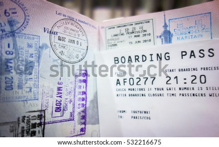 Airplane boarding pass and heavily stamped passport indicating frequent travel. #532216675