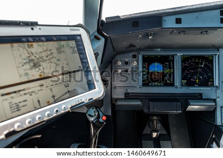 Airplane Cockpit, Captain site with the Primary Flight Display and navigation display in front and the computer with navigational charts just above the side stick  #1460649671