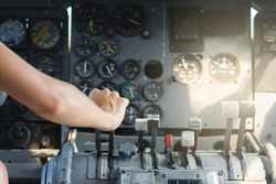 Airplane Cockpit thrust levers with female hand on top for takeoff