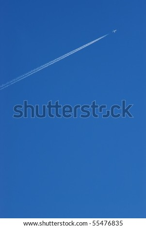 Airplane contrail against blue sky with copy space