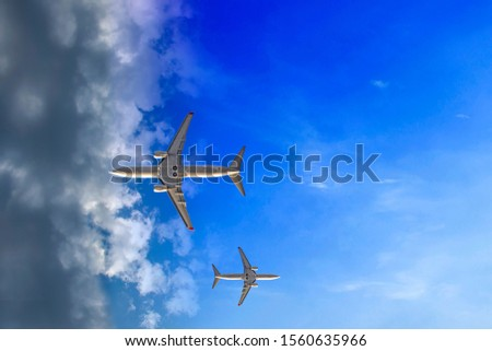 Airplane entering the clouds. Air traffic. Airplanes enter the cloud, every in own way. Writing area #1560635966