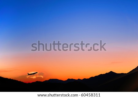 airplane flaying in a sunset sky over mountain landscape