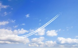 airplane flies in white clouds in a blue sky and leaving trail