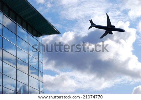 Airplane flies over glass window office building - stock photo