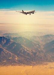 Airplane flight over the mountain peaks in sahara desert. Landscape with charter flights over the highlands for your concept of the passenger air freight or travel poster.