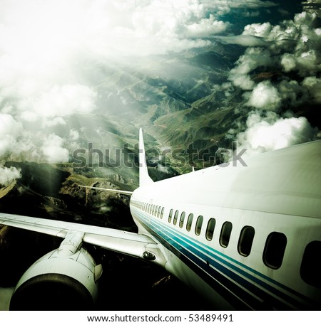 airplane fly above the mountain with clouds.