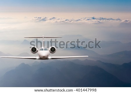 Airplane fly over clouds and Alps mountain on sunset. Front view of a big passenger or cargo aircraft, business jet, airline. Transportation, travel concept