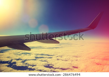 Airplane flying above clouds at pink sunrise