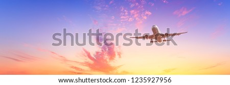 Airplane flying above dramatic clouds during sunset