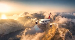 Airplane flying above mountains and low clouds at sunset in Spain. Landscape with passenger aircraft, cloudy sky, rocks, forest and sunlight. Business travel in commercial plane. Aerial view. Journey