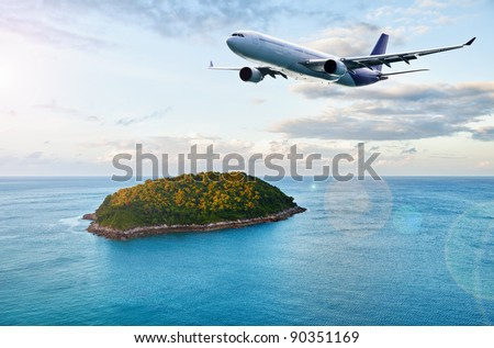 Airplane flying above ocean with beautiful small island.