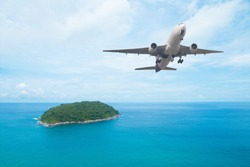 Airplane flying above sea blue island - Travel concept