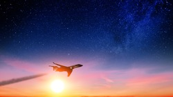 Airplane flying at beautiful sunset against dark night starry sky background. Aerial side view of business jet aircraft at dusk with smoke contrails on stars skyline. Modern passenger plane in air