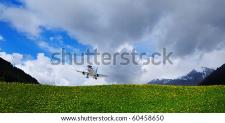 airplane flying in a cloudy sky above green hills