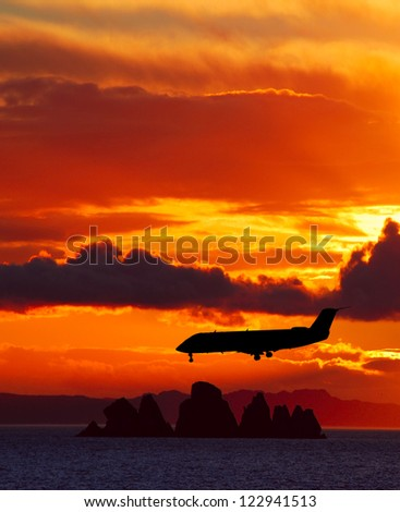 Airplane flying low over an island at sunset - stock photo