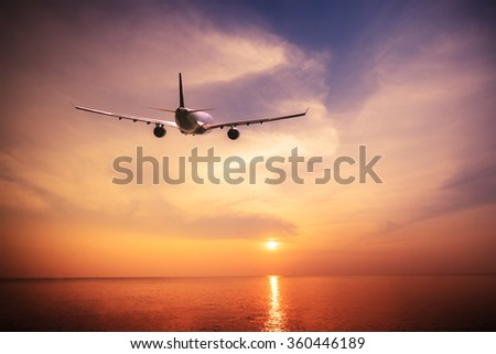 Airplane flying over amazing tropical ocean at  sunset. Thailand travel  landscapes and destinations