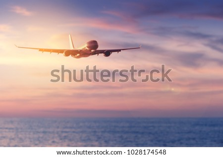 Airplane flying over blur tropical beach and sunset sky abstract background.Copy space of business summer vacation and travel adventure concept.Vintage tone filter effect color - Shutterstock ID 1028174548