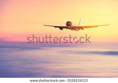 Airplane flying over blur tropical beach with smooth wave and sunset sky abstract background. Copy space of business summer vacation and travel adventure concept. Vintage tone filter effect color. - Shutterstock ID 1028226121
