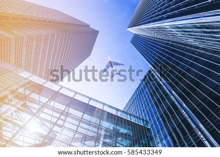 Airplane flying over business skyscrapers. #585433349