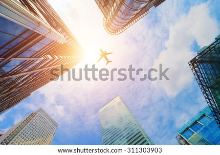 Airplane flying over business skyscrapers, high-rise buildings. Transport, transportation, travel. Sun light on blue sky.