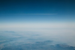 Airplane flying over foggy mountains with white trail in blue sky