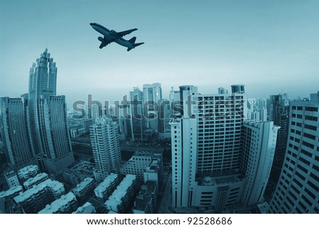 Airplane flying over high buildings