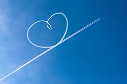 Airplane flying through clear blue sky left heart shape of vapour trails behide. Heart shapes on the sky from the planes traces.