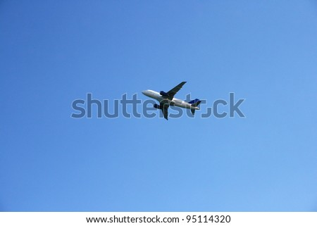 Airplane flying up in blue sky.