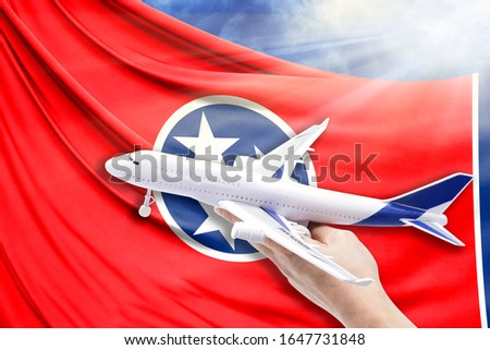 Airplane in hand with national flag State of Tennessee on a background of blue sky with sunbeams stock photo