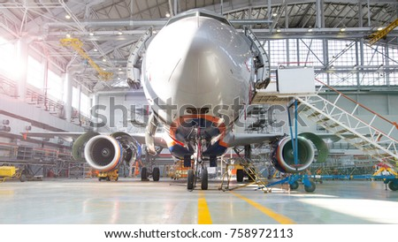 Airplane in hangar, front view of aircraft and light from windows