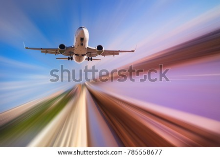 Airplane in motion over roadway on blur blue sky background #785558677