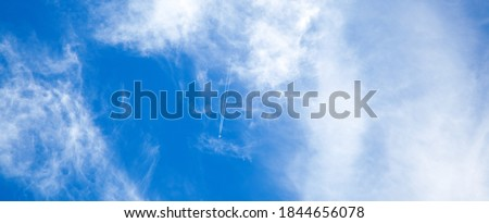 Airplane in the blue sky with clouds from below, high flying passenger plane with condensation trail. jet plane flying overhead diagonally in sky with sunlight. Bottom view Stock photo ©