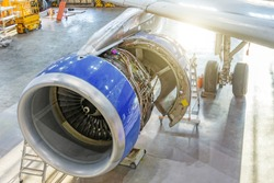 Airplane in the hangar for maintenance, view of the engine wing with the hood open