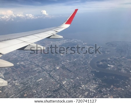 Airplane in the sky, fly airplane across the city,airplane Wing ,airplane and sky,Airplane and city,airplane,landscape from window airplane #720741127
