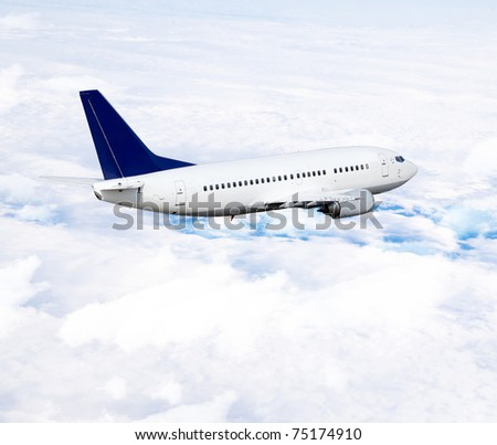 Airplane in the sky, over the cloudy sky