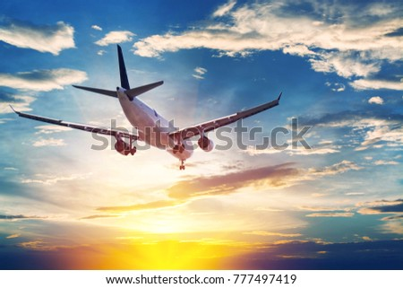 Airplane in the sunset sky flight travel transport airline background concept.
