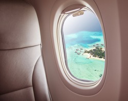 Airplane interior with window view of Maldives island. Concept of travel and air transportation