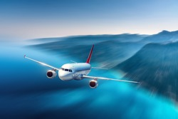 Airplane is flying over blue sea and mountains at sunset. Landscape with passenger airplane, island at dusk. Passenger aircraft  with motion blur effect. Business travel. Aerial view. Commercial plane