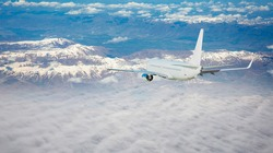 Airplane is flying over low clouds and snowy mountains -