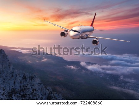 Airplane is flying over low clouds at sunset. Landscape with passenger airplane, mountains, sea and orange sky with red clouds in summer. Passenger aircraft. Business travel in Europe.Commercial plane